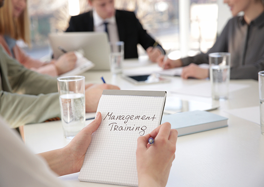 Woman holding notebook with text MANAGEMENT TRAINING at business presentation